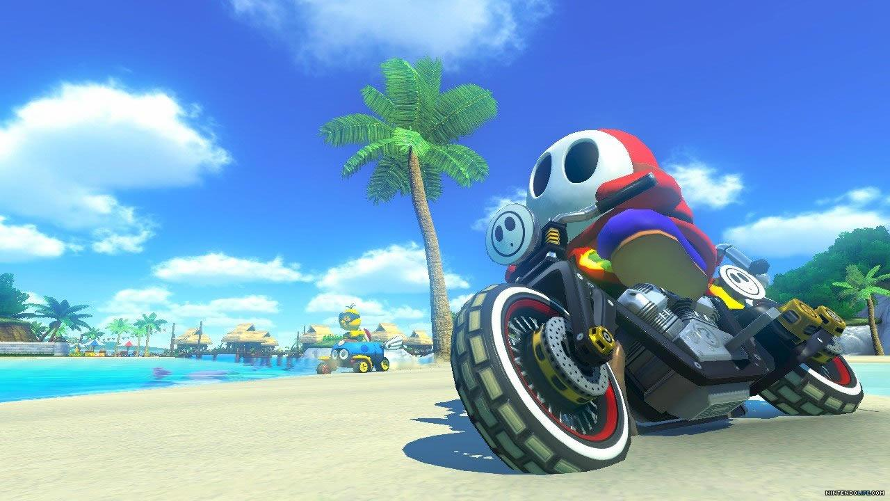 Shy Guy riding his motorbike on a beach track in Mario Kart 8